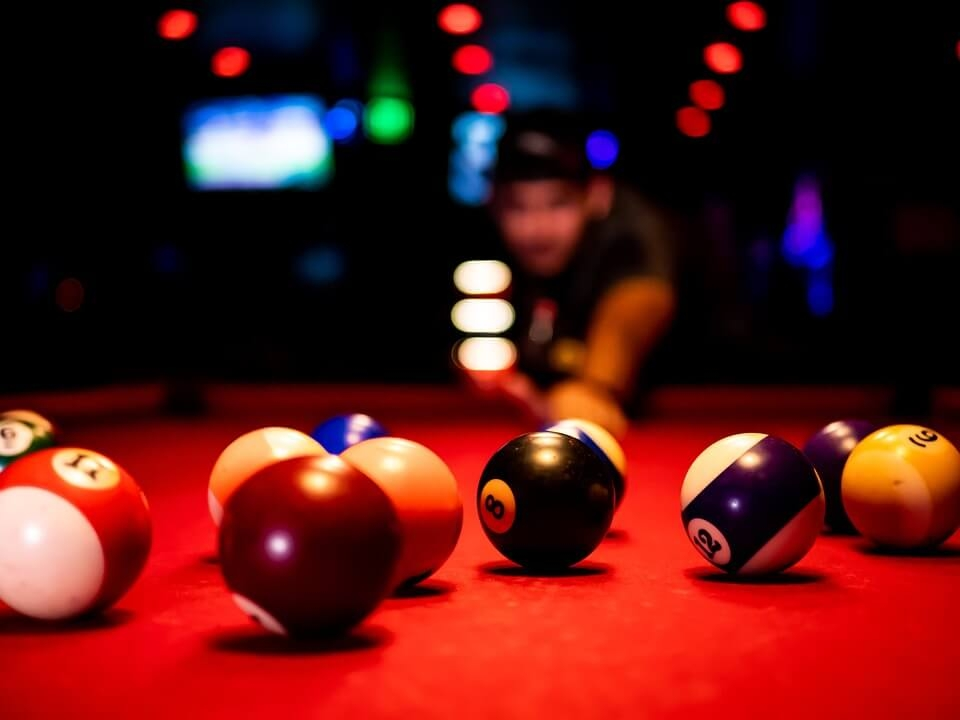 Pool balls on a table with out of focus player in the background