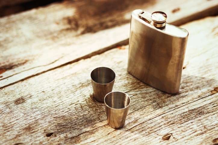 A hip flask on a wooden table next to two shot glasses
