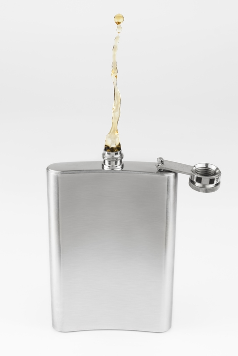 Alcohol pouring out of a hip flask