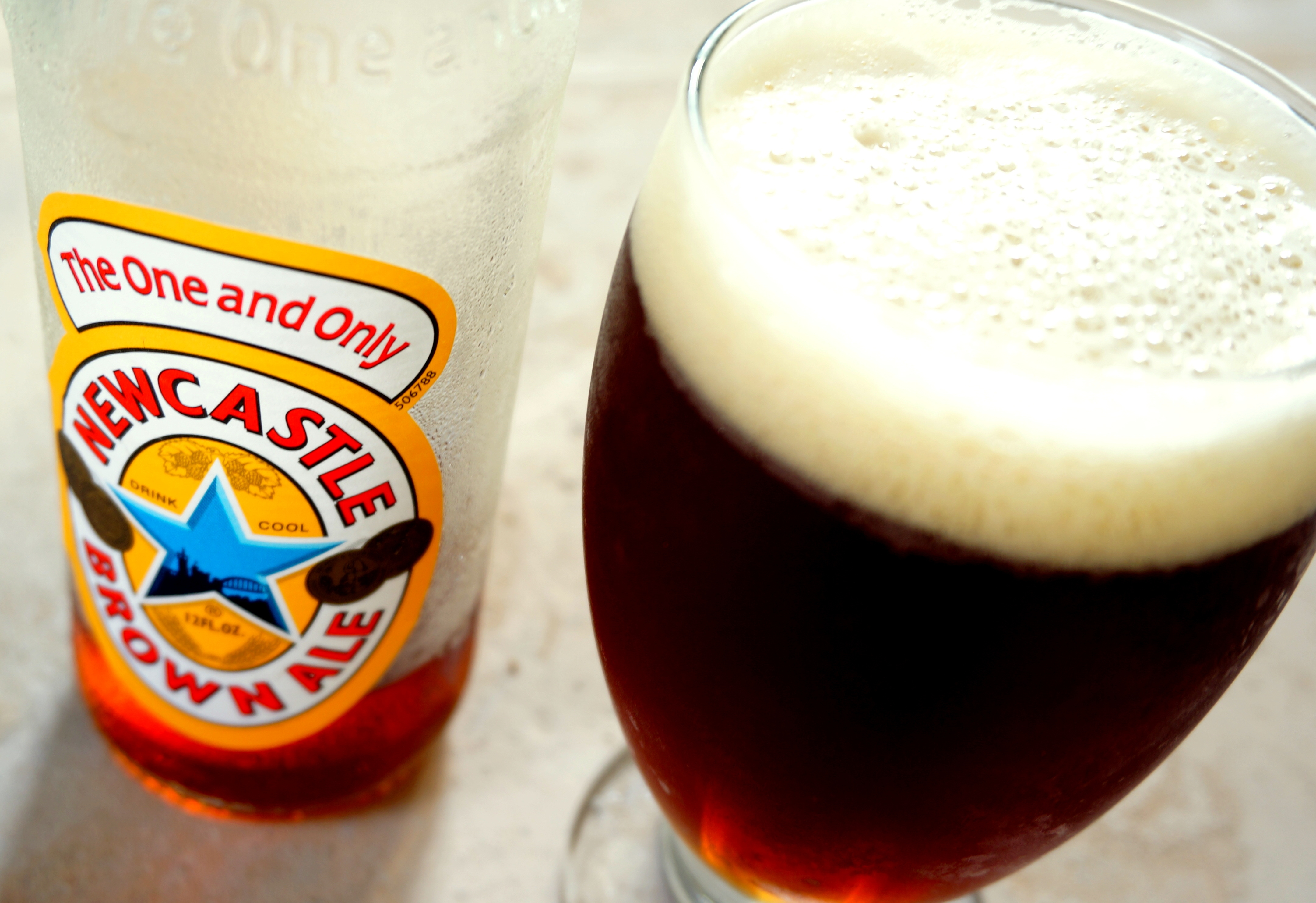 A bottle of Newcastle brown ale poured into a glass