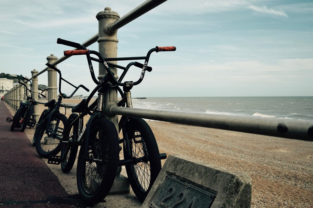 BMX bikes leaning against a fence on the beach