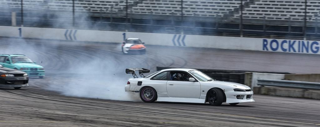 A white drift car drifting at a race track