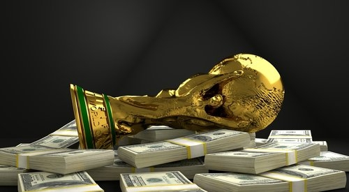 The FIFA World Cup Trophy on a pile of Money