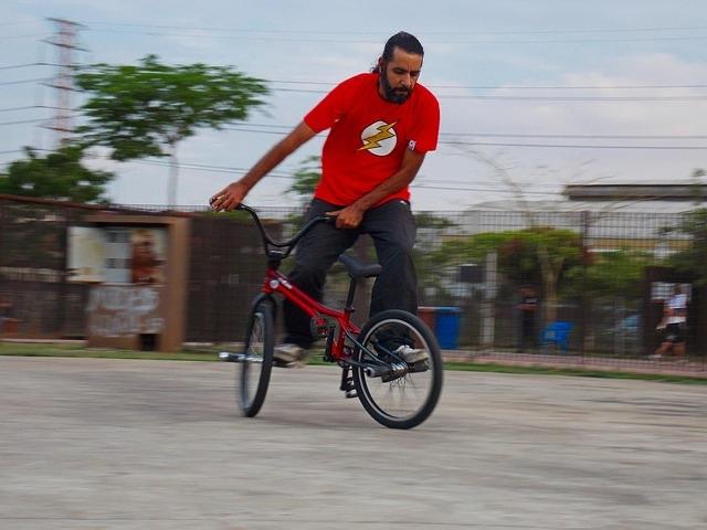 A flatland BMX rider balancing on his pegs