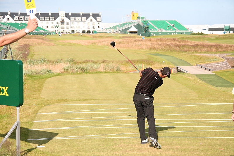 A golfer strikes a ball at Carnoustie golf course towards the club house