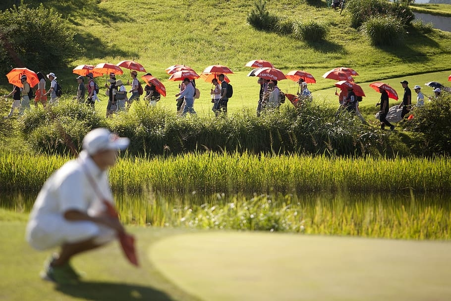 Spectators walking past a golfer