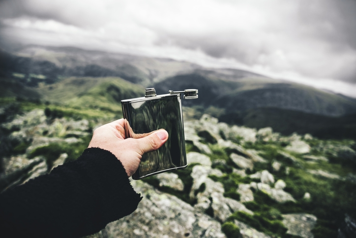 Holding a drinking flask out over a mountain range