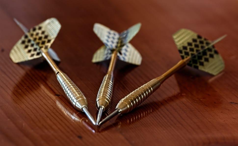 Three gold darts meet at the tip
