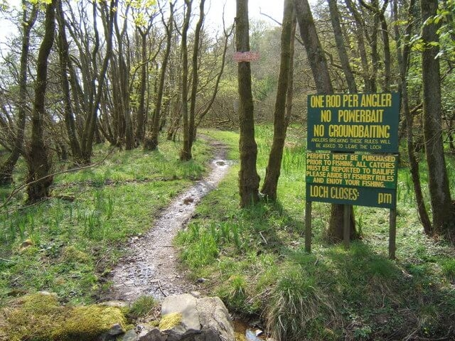 Trail towards a fishing lake with rules displayed on a sign.