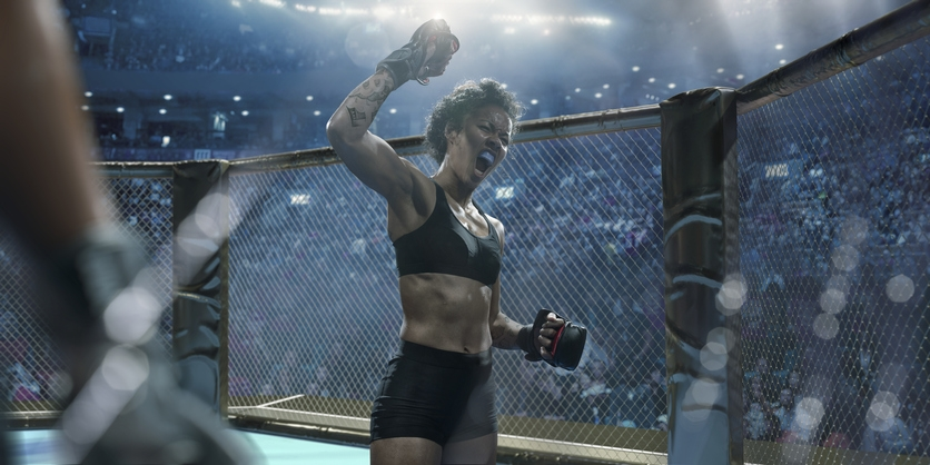 A Female MMA fighter Celebrating in the octagon
