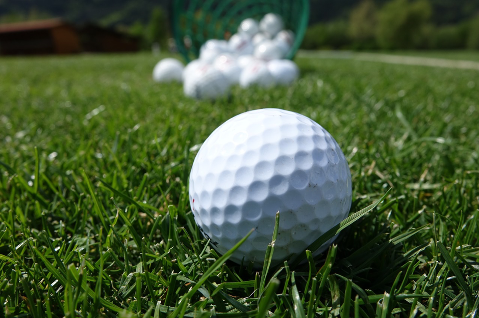 golf ball on grass in from of a basket of golf balls on a sunny day