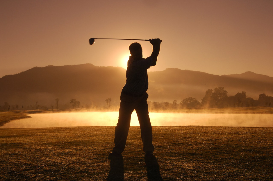 a silhouette of a man striking a golf ball next to a lake