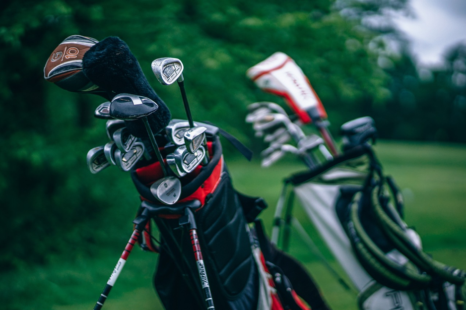 Two bags of golf clubs on a gold course