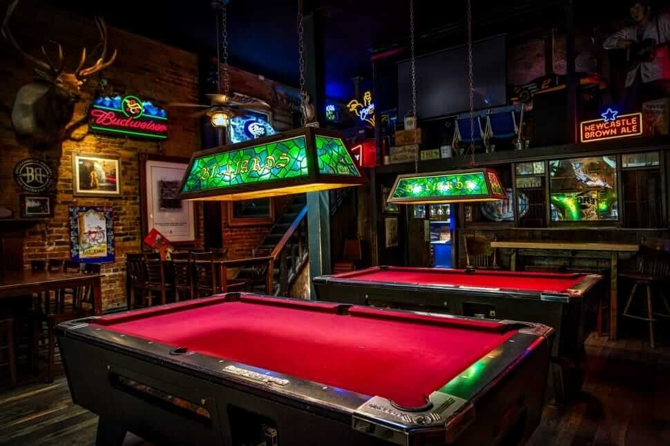 Dimly lit pool room with two red pool tables