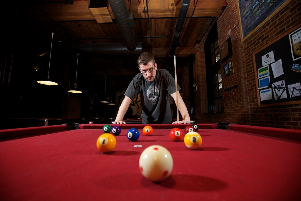 Pool player leans over table