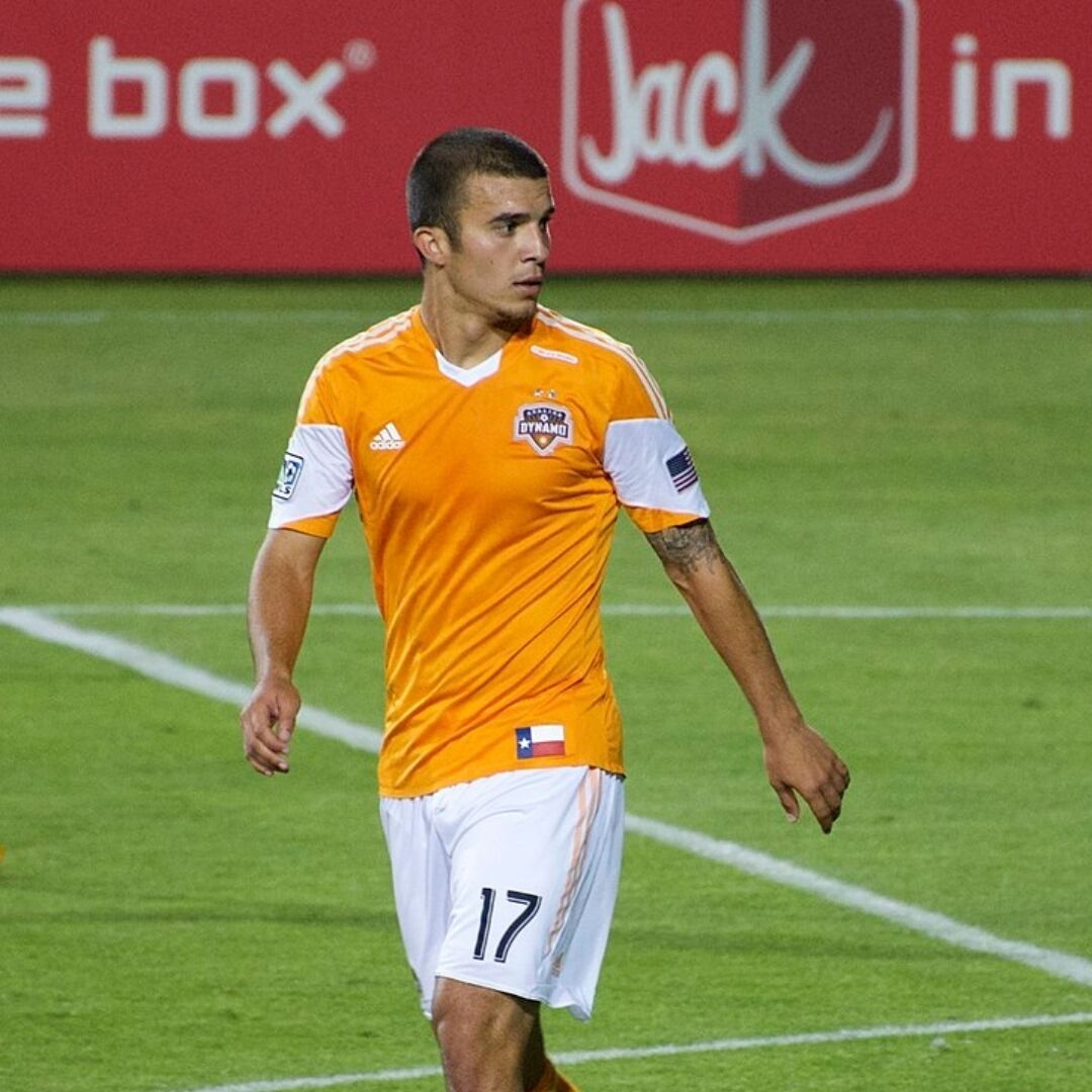 Alex Morgan's Husband, Servando Carrasco in an orange kit on a football pitch