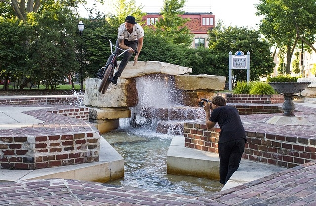 A street BMX rider doing a barspin over a water fountain