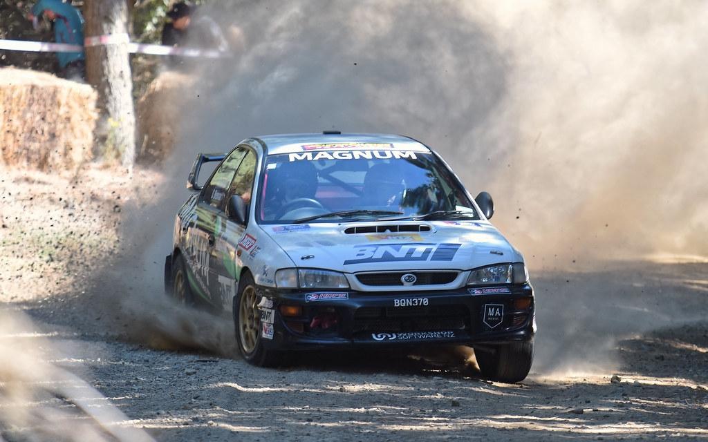 A Subaru rally car drifting around a corner