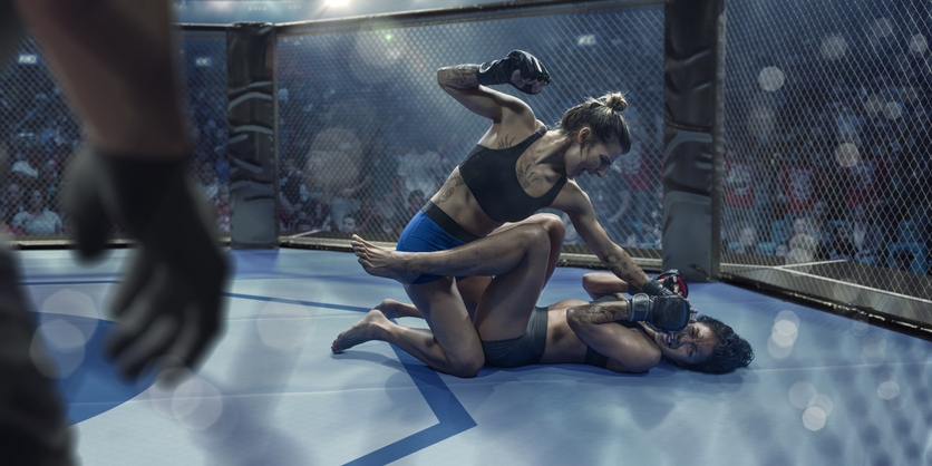One female MMA fighter pinning another in the octagon
