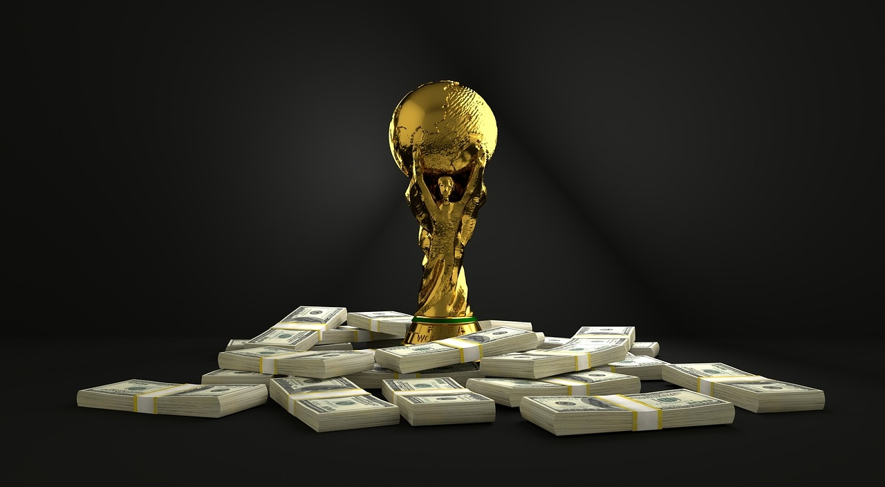 THE FIFA WORLD CUP TROPHY ON TOP OF A PILE OF MONEY