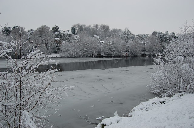 A half-frozen, snow-covered Carp fishing lake in winter.