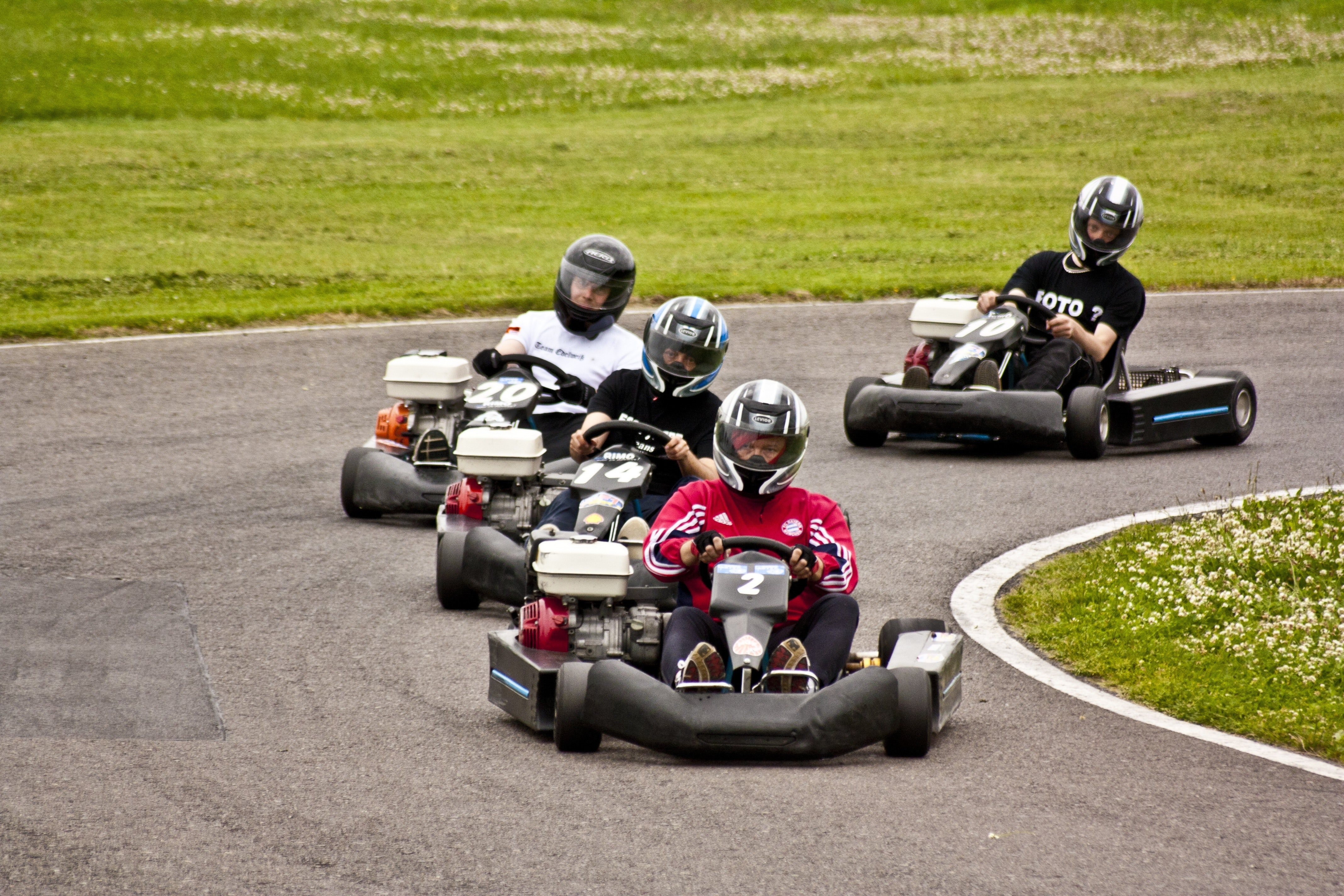 Four people Go-Karting on an outside track