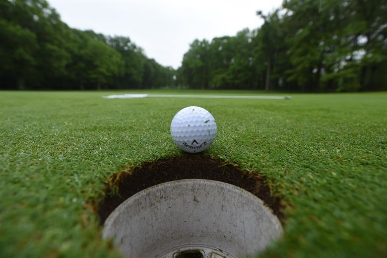A golf ball on the edge of falling into the hole.