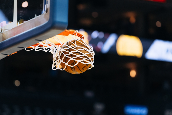 A basketball swishing through the net of the hoop at a basketball stadium