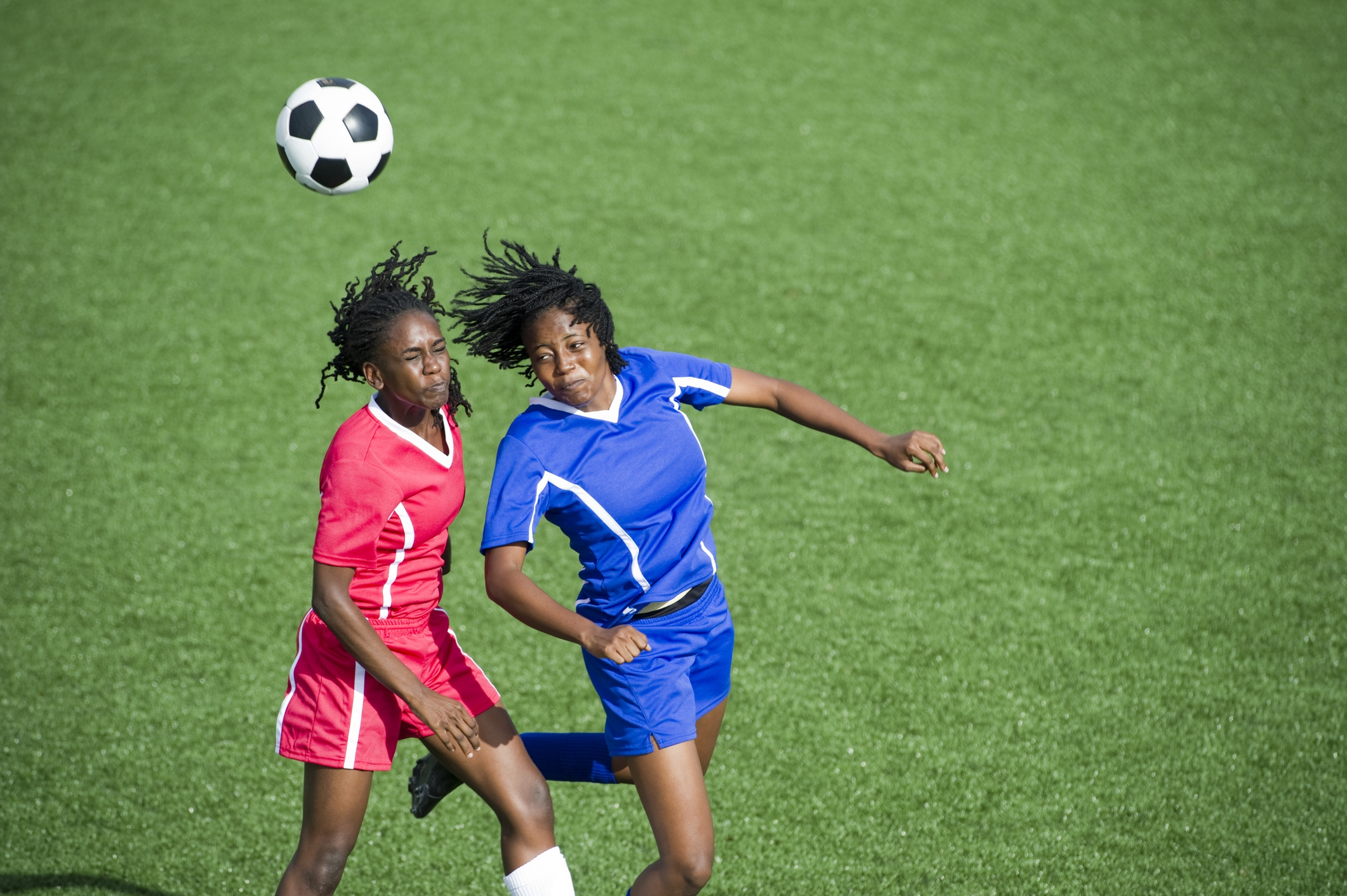 Two professional women football players heading a ball
