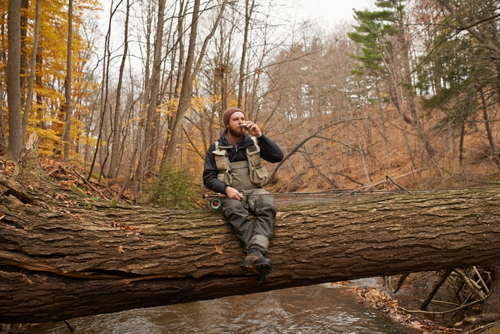 A Fisherman drinking from a hip flask sat on a log over a river