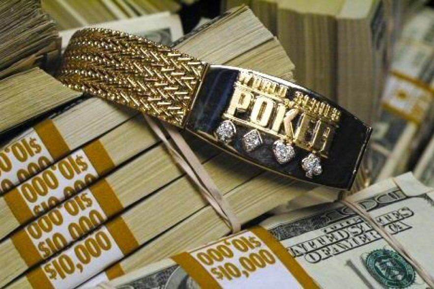 The WSOP bracelet on top of a pile of money