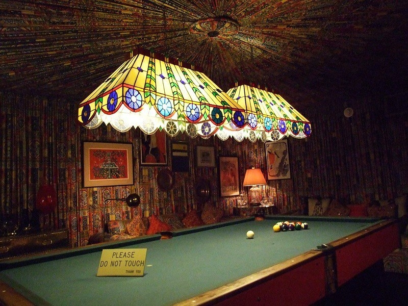 """Bohemian pool room with """"Do not touch"""" sign on table"""