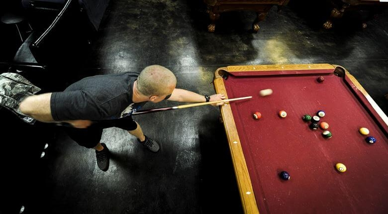 Man taking a shot on a red pool table